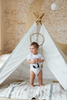 Little boy playing in a tent in loft interior with brick wall.