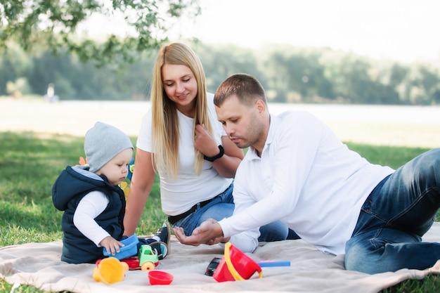 おもちゃの車を遊んで、屋外で彼の父と母と楽しんでいる小さな男の子