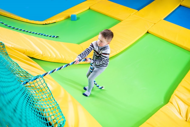 Little boy playing in trampoline center jumping and climbing with rope