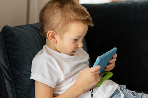 Маленький мальчик играет в видеоигры по телефону