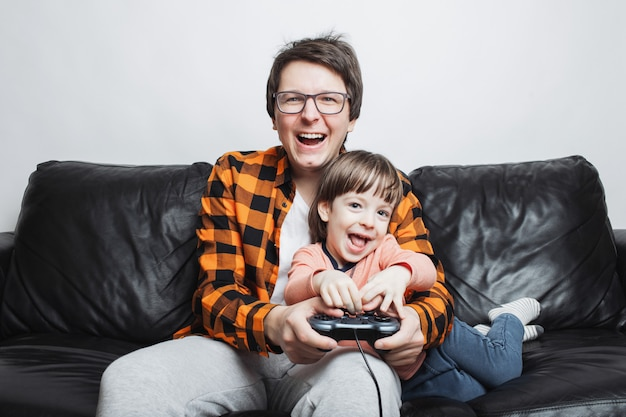 A little boy playing video games with dad.