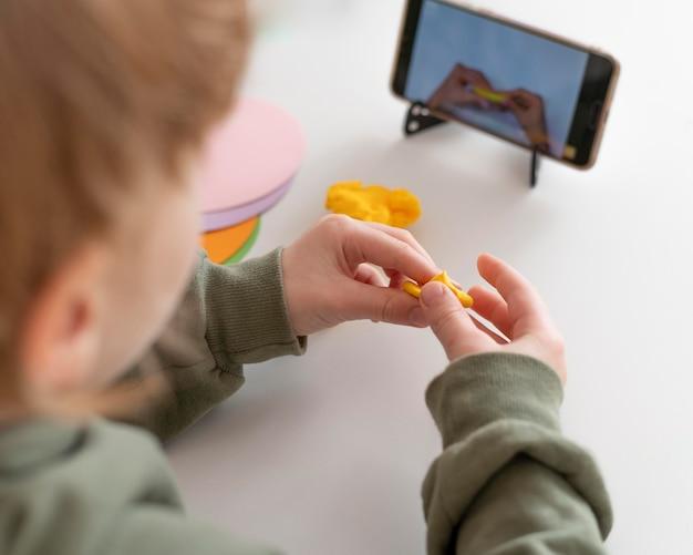 Маленький мальчик играет, глядя на смартфон