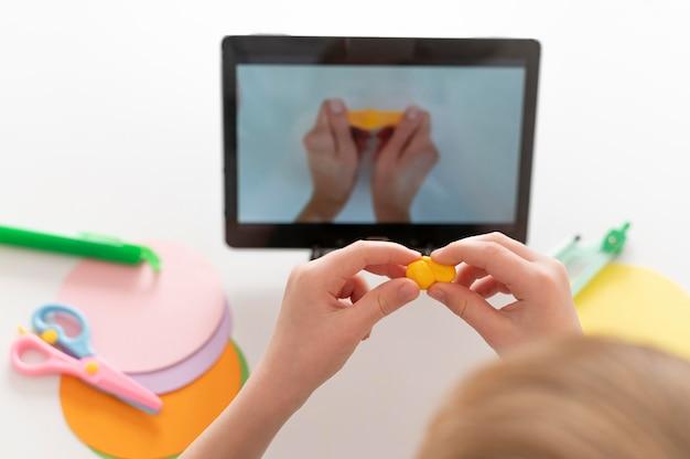 Маленький мальчик играет, глядя на планшет