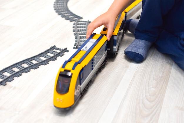 床でおもちゃの電車で遊ぶ男の子