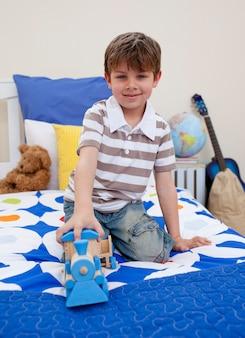 그의 침실에서 기차를 가지고 노는 어린 소년 프리미엄 사진