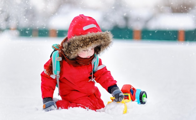 Little boy playing with bright car toy and fresh snow