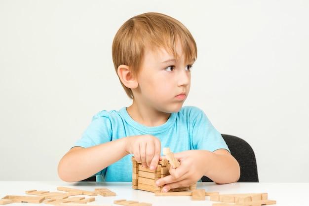 Маленький мальчик играет со строительными блоками на столе