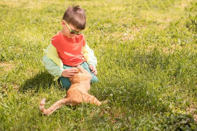 Маленький мальчик играет с кошкой