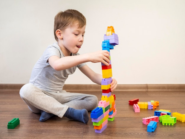 Little boy playing with colorful block game on the floor