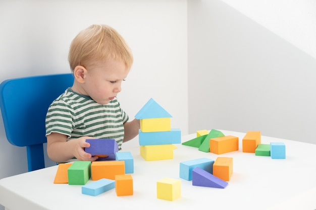 흰색 바탕에 테이블에 화려한 블록을 가지고 노는 어린 소년. 프리미엄 사진