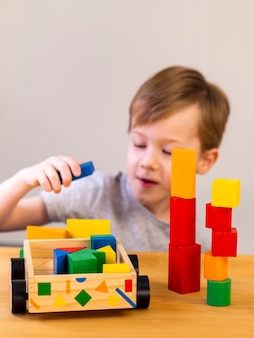 Little boy playing with colorful cubes and wooden car