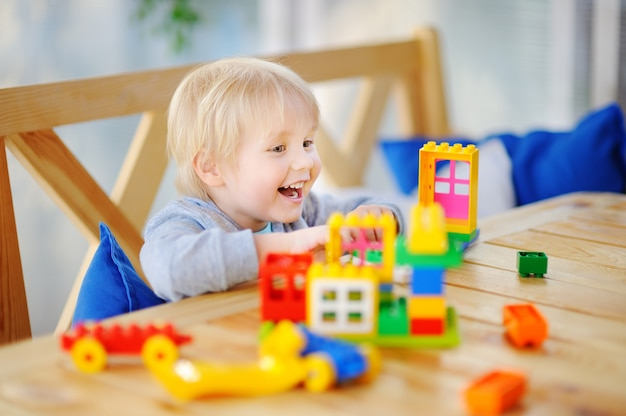Little boy playing with colorful plastic blocks at kindergarten or at home