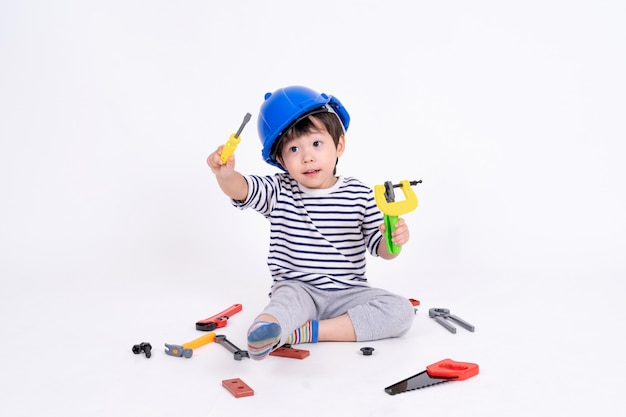 Little boy playing with construction equipment on white