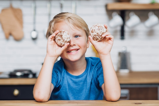 Little boy playing with cookies