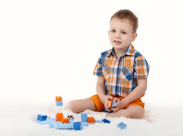 Little boy playing with designer on the floor on white