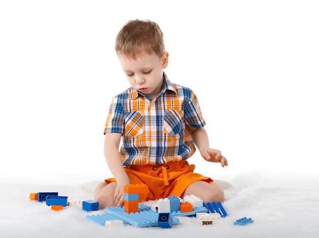 白で隔離の床でデザイナーと遊ぶ小さな男の子