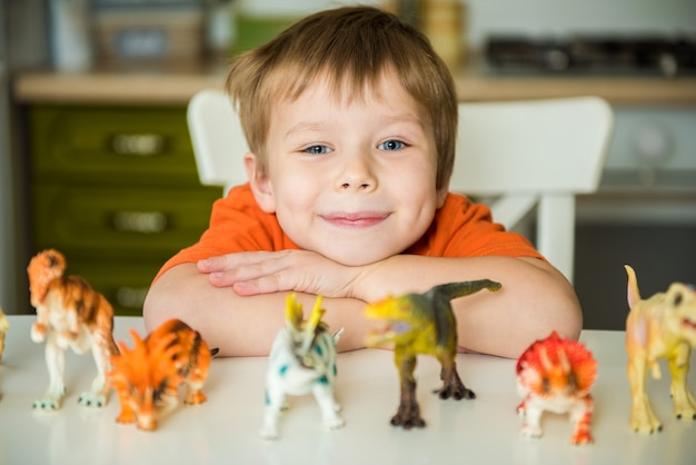 Little boy playing with dinosaurs. lizard collection
