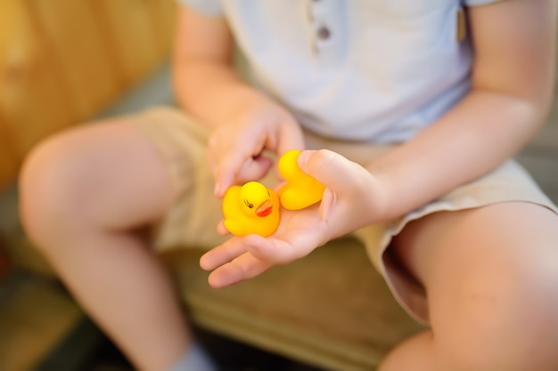 Little boy playing with family of rubber duck