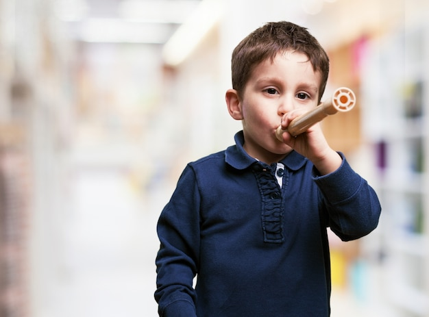 Little boy playing with a flute