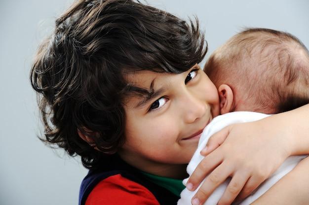 彼の新しい赤ん坊の兄弟と遊んでいる少年
