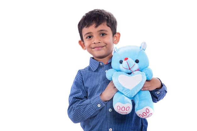 Little boy playing with his stuffed teddy bear on white wall