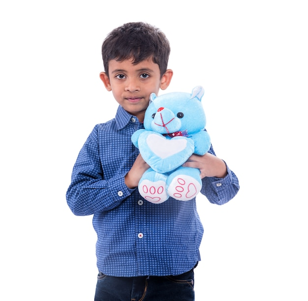 Маленький мальчик играет со своим плюшевым мишкой
