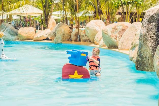 Маленький мальчик играет с надувными игрушками в бассейне аквапарка в яркий солнечный летний день