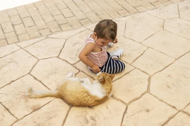 Маленький мальчик играет с домашним животным на заднем дворе