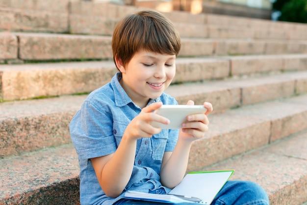 Маленький мальчик играет со смартфоном на открытом воздухе