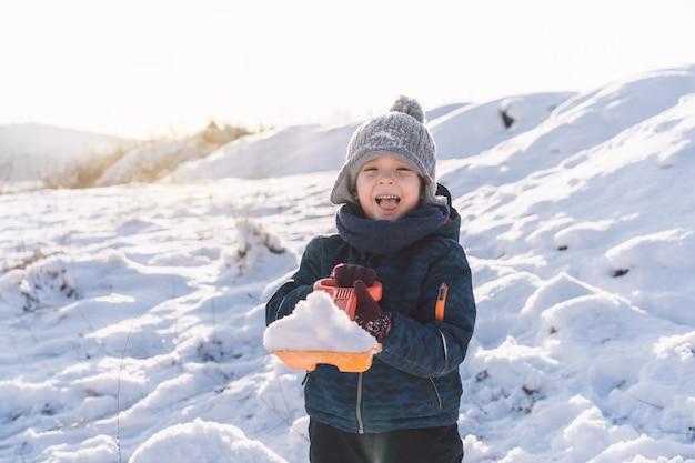Маленький мальчик играет со снегом