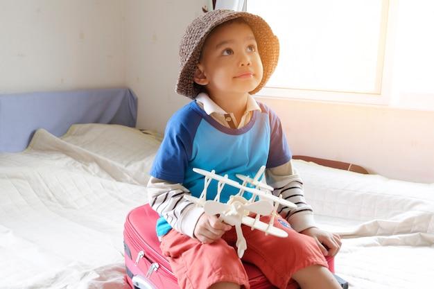 Маленький мальчик, играющий с игрушечным самолетом, концепция путешествий и приключений