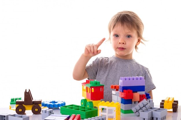 Little boy playing with toy blocks pointing his finger up, concentrated face isolated
