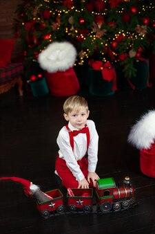 Маленький мальчик играет с игрушечным рождественским паровозом
