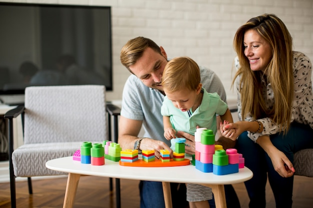 Little boy playing with toys in the living room with father and mother