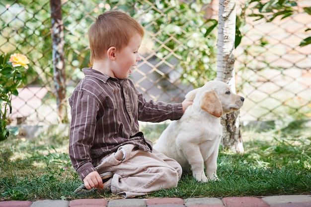 Little boy playing with a white puppy