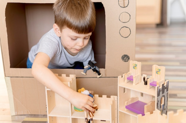 Little boy playing with wooden castle