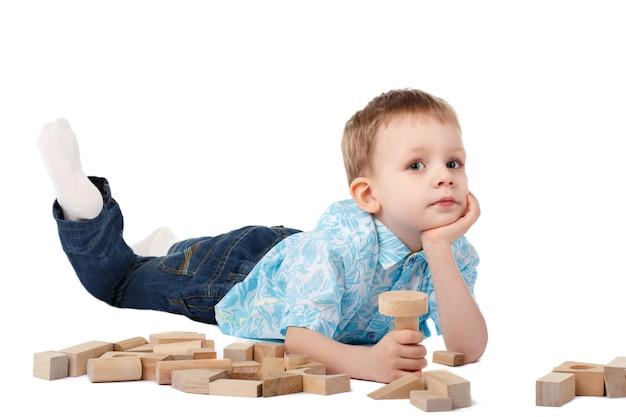 白で隔離の床で木製のデザイナーと遊ぶ小さな男の子