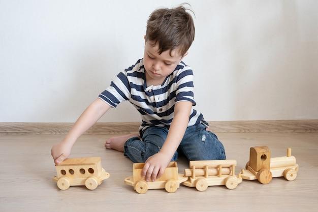 木製の電車で遊んでいる少年。エコおもちゃ。