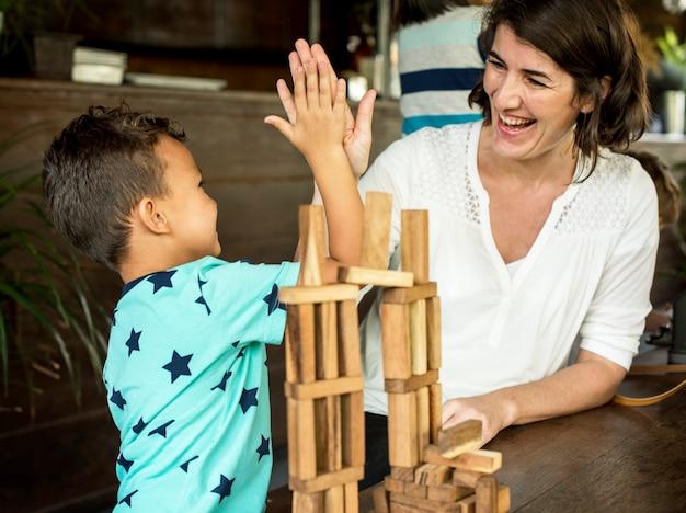 Маленький мальчик играет игрушку из деревянных блоков с учителем