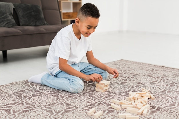Little boy playing a wooden tower game