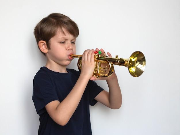 Маленький мальчик играет на игрушечной трубе