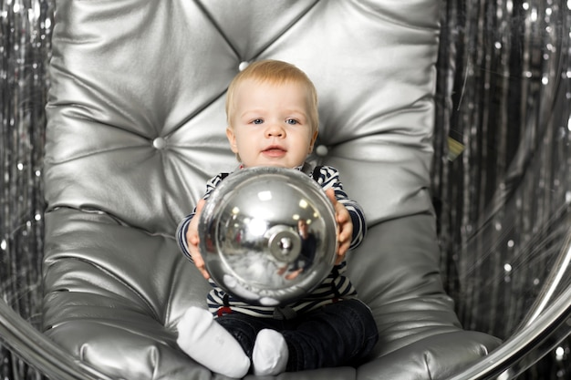 Little boy plays in a chair a glass bowl with silver balls.