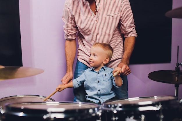 Little boy plays drums in recording studio.