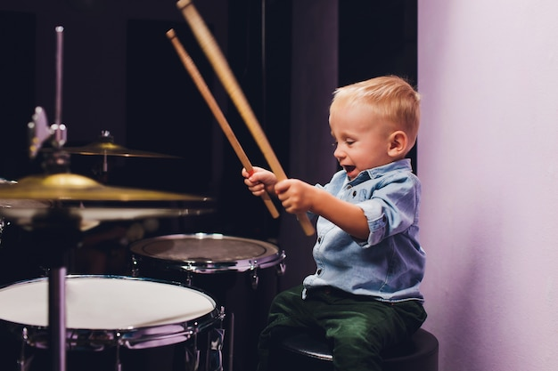 Little boy plays drums in recording studio.