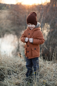 A little boy plays in a field in autumn in a brown jacket and hat.