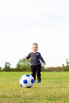 小さな男の子がサッカー場でサッカーをし、パスを打つと、ボールがフィールドを横切って走り、新鮮な空気の中でゴールを決めます。
