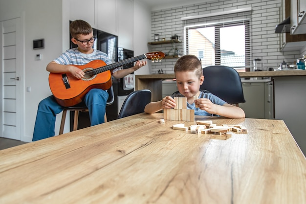 A little boy plays the guitar, and his brother builds a turret with wooden cubes at home at the table.