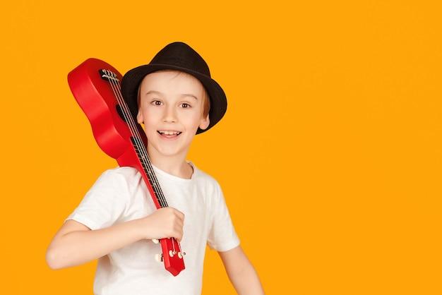 小さな男の子はハワイアンギターやウクレレで演奏します。音楽を楽しんでいる幸せな子供。ウクレレを弾くことを学ぶ学生。オレンジ色の背景に分離された夏の帽子のファッショナブルな男の子。