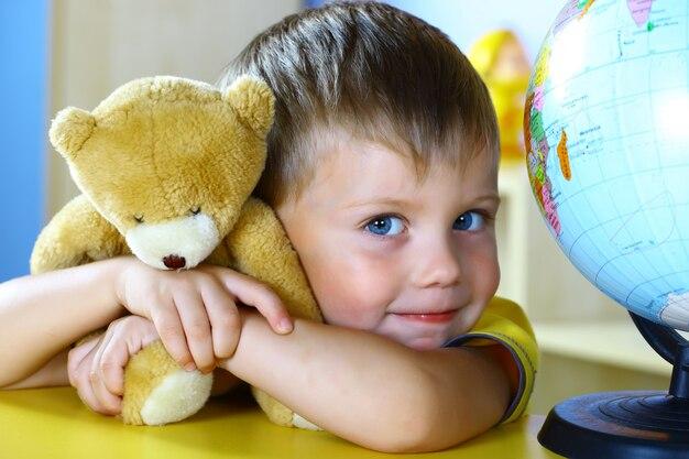 Маленький мальчик играет с мишкой