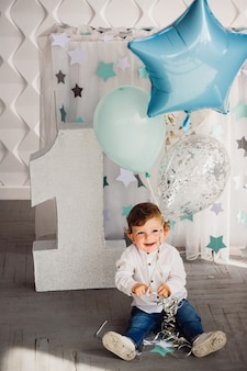 Little boy plays with blue balloons befoe large number one in a cosy room